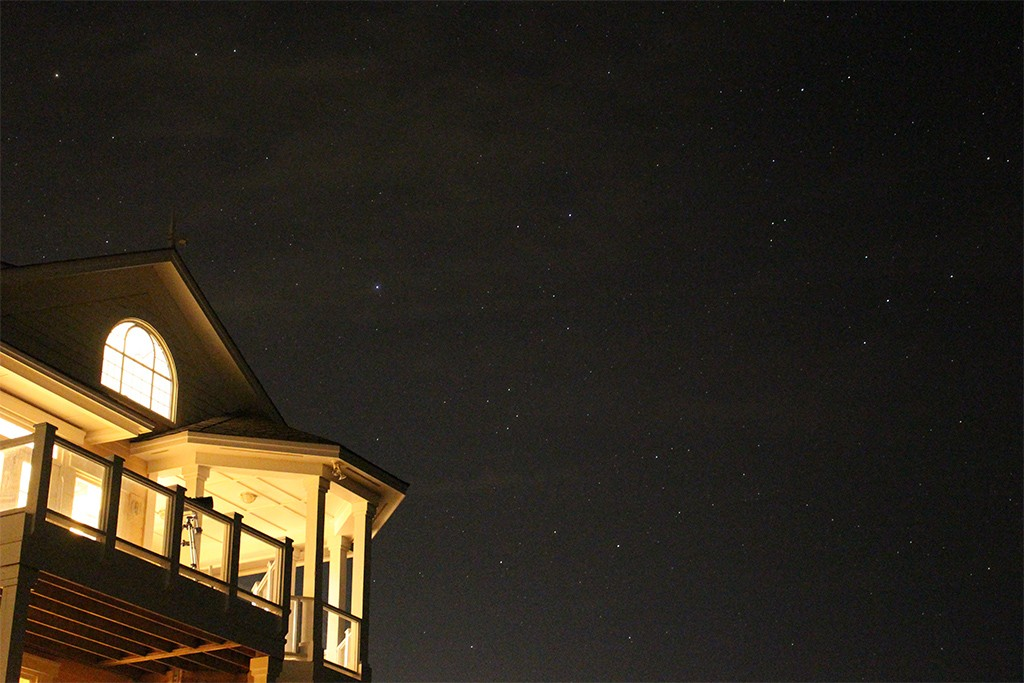 View of the night sky and the upper porch of a house with a telescope